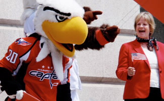 "Helen Marano (right), Director, Office of Travel and Tourism Industries, with Washington Capitals mascot ""Slapshot"" on the steps of the National Portrait Gallery while participating in U.S. Travel Rally Day. (U.S. Department of Commerce photograph.)"