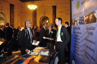 Attendees at the Sustainability Summit exchange explore the displays in the Commerce Department's lobby