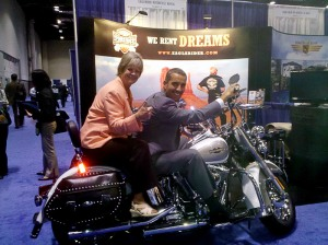 OTTI director Helen Marano and ITA Global Travel and Tourism team member Tony Michalski test out a Harley Davidson at Pow Wow in Orlando 2010