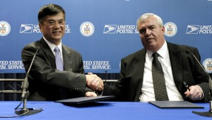 Commerce Secretary Gary Locke and U.S. Postmaster General John Potter shake hands after signing agreement.