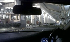 View of Delhi International Airport terminal from inside a car.