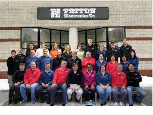Employees of Patton Electronics Company together with co-owner Bobby Patton (center)