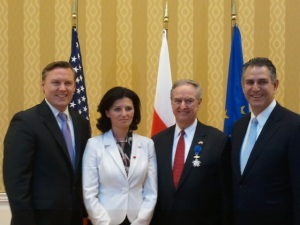 Jay Burgess (second from right) recieves the Order of Merit of the Republic of Poland with Adam Wilczewski (left), Vice Minister of State for the Ministry of the Economy Ilona Antoniszyn-Klik, and Under Secretary Francisco Sánchez.