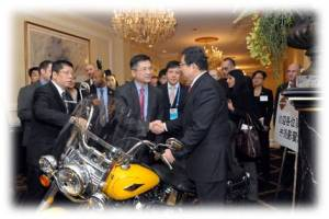 Shaking hands over a Harley-Davidson Softail are China's Minister of Commerce, Chen Deming (right), and former Secretary of Commerce, current U.S. Ambassador to China, Gary Locke (center) (Photo Commerce)