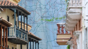 Image of a street in Colombia with a map in the background.