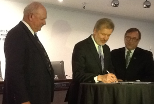 Clark County Commissioner Tom Collins, Acting Deputy Under Secretary for International Trade Ken Hyatt, and LVCVA President/CEO Rossi Ralenkotter sign a Memorandum of Agreement between ITA and LVCVA.