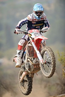 A dirk biker is executing a jump on a dirt course.