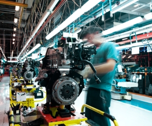 A manufacturing worker works on an automobile engine.