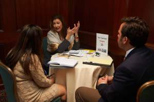 Image of three people meeting at a table and having a discussion at Discover Global Markets in New York