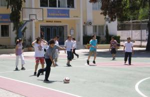 Kids play soccer outside a school in Athens.