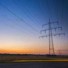Electric wires running from a tower with the sky in the background