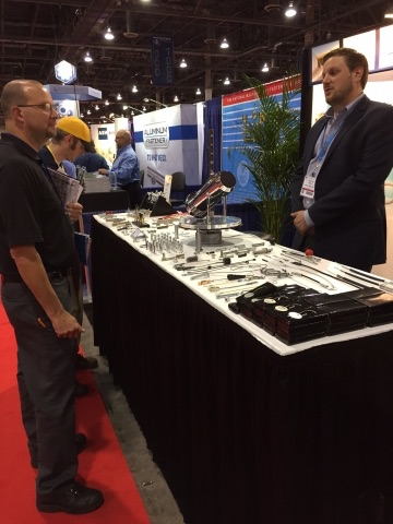 Jordan Jaeger discusses Pivot Point Fastening Solutions with a trade show attendee in Las Vegas