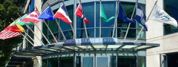 Main Entrance of the World Trade Center Seattle with Flags of Different Countries and the Port of Seattle.