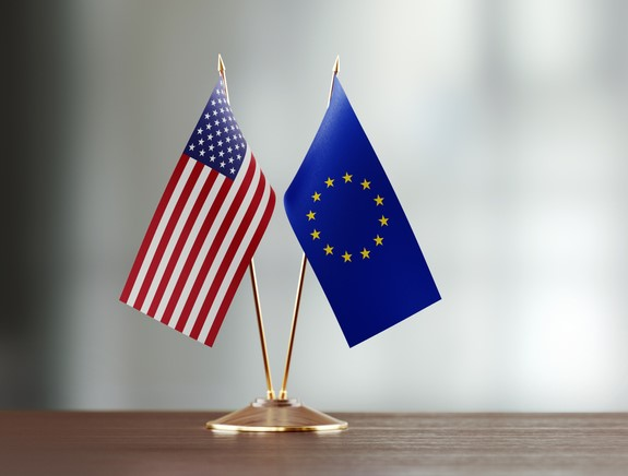 American And European Union Flag Pair On A Desk Over Defocused Background