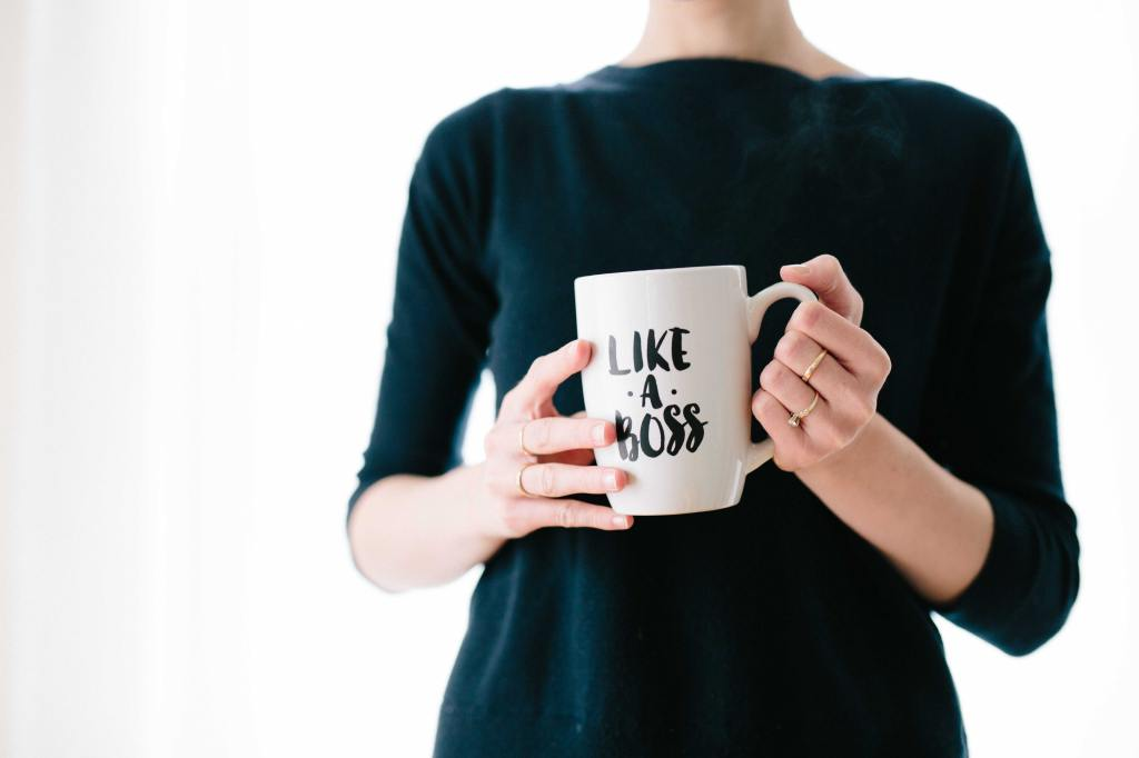"Female executive holding a coffee mug that says ""Like A Boss"" on it. Souce: Unspash.com"