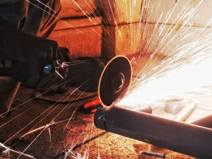 Circular saw cutting through a pipe throwing off sparks. Image from Unsplash.com