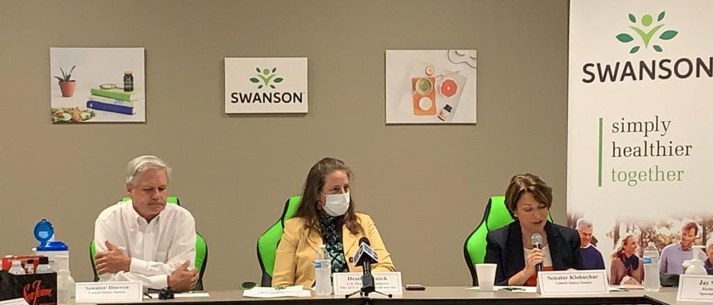 An image of Senator Hoeven (left), Heather Ranck (center), and Senator Klobuchar (right) seated. Senator Klobuchar is holding a microphone.
